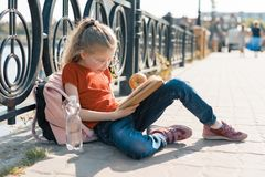 Outdoor portrait of little schoolgirl with book, girl child 7, 8 years old with glasses backpack reading textbook.  royalty free stock photo