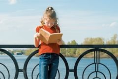 Outdoor portrait of little schoolgirl with book, girl child 7, 8 years old with glasses reading textbook.  stock images