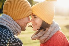 Outdoor portrait of lovely female and her boyfriend, look at each other`s eyes, keep noses together, enjoy calmness and togetherne royalty free stock images