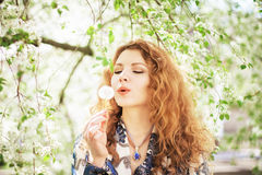 Outdoor portrait of a lovely woman with dandelion Royalty Free Stock Photos