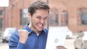 Outdoor Portrait of Man Cheering for Success on Tablet. 4k high quality, 4k high quality stock video