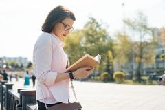 Outdoor portrait of mature caucasian woman 40, 45 years old with glasses reading book stock images