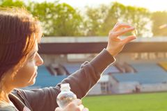 Outdoor portrait of mature woman taking vitamin E capsule pill of cod liver oil, at the stadium. Royalty Free Stock Images