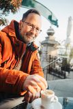 Outdoor portrait of 50 year old man. Outdoor portrait of middle age man wearing eyeglasses and orange winter jacket. Drinking coffe in outdoor cafe royalty free stock image