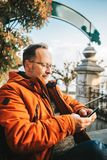 Outdoor portrait of 50 year old man. Outdoor portrait of middle age man wearing eyeglasses and orange winter jacket, holding smartphone royalty free stock images