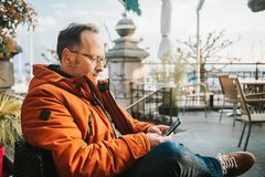 Outdoor portrait of 50 year old man. Outdoor portrait of middle age man wearing eyeglasses and orange winter jacket, holding smartphone stock photo