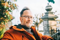 Outdoor portrait of 50 year old man. Outdoor portrait of middle age man wearing eyeglasses and orange winter jacket stock image