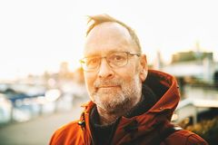 Outdoor portrait of 50 year old man. Outdoor portrait of middle age man wearing eyeglasses and orange winter jacket stock photos