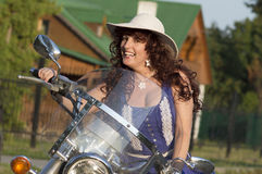 Outdoor portrait of the middle age woman on the motorcycle. Royalty Free Stock Images