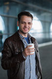 Outdoor portrait of modern young man with coffee to go cup, smiling Royalty Free Stock Images