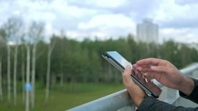 Outdoor portrait of modern young man with digital tablet.Against the background of green trees and beautiful blue clouds. Close-up stock video