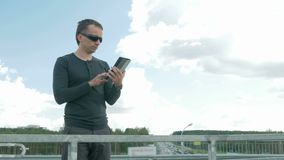 Outdoor portrait of modern young man with digital tablet. A man with glasses on the bridge. Behind the blue sky.  stock footage