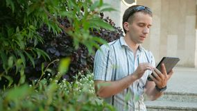 Outdoor portrait of modern young man with digital tablet. Man in sunglasses and jacket. Around a lot of green plants.  stock video