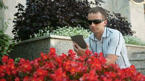 Outdoor portrait of modern young man with digital tablet. Man in sunglasses and jacket. Near a lot of red flowers.  stock footage
