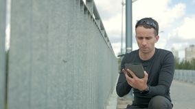 Outdoor portrait of modern young man with digital tablet. Railing of the bridge, near the road and the beautiful blue. Clouds in the background stock video footage