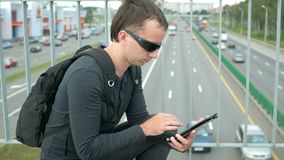 Outdoor portrait of modern young man with digital tablet in the street. The man in glasses with backpack sitting on the. Bridge. Bottom drive cars stock video