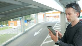 Outdoor portrait of modern young man with digital tablet in the street. The man in glasses with backpack sitting on the. Bridge. Bottom drive cars stock video footage