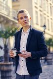 Portrait of modern young man with mobile phone in the street. Outdoor portrait of modern young man with mobile phone in the street Royalty Free Stock Images