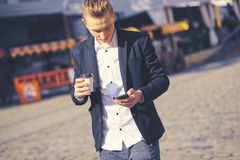 Portrait of modern young man with mobile phone in the street. Stock Photo