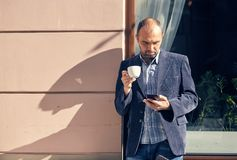 Portrait of modern young man with mobile phone in the street. Outdoor portrait of modern young man with mobile phone in the street Royalty Free Stock Photo