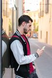 Outdoor portrait of modern young man with mobile phone stock photography