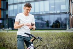 Outdoor portrait of modern young man with mobile phone in the street, sitting on bike.  Stock Photography