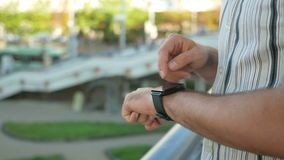 Outdoor portrait of modern young man with smart watch in the street. Against the background of people walking and stock footage