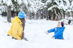 Outdoor portrait Mother and child playing in the winter park. showered with snow stock photo