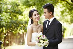 Outdoor portrait of a newly-wed asian couple stock photo