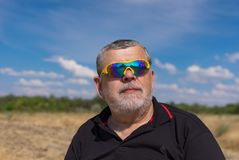 Free Outdoor Portrait Of A Bearded Senior In Sunglasses Against Blue Cloudy Sky Royalty Free Stock Image - 122132416
