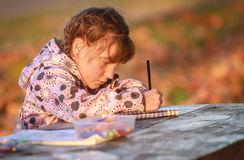 Outdoor Portrait Of Young Happy Child Girl Drawing Or Writing In Stock Images