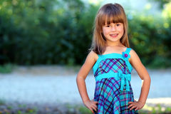 Outdoor portrait of optimistic smiling pretty little girl in blu Stock Photo