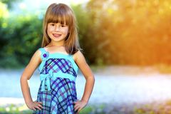 Outdoor portrait of optimistic smiling pretty little girl in blu. E dress Stock Photos