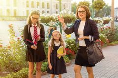 Outdoor portrait of a parent and children on the way to school. Urban background Royalty Free Stock Photos