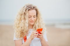 Outdoor portrait of pleasant looking curly female uses modern cell phone for online communication, being always in touch, has vaca royalty free stock photography