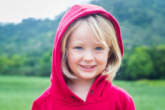 Outdoor portrait portait of cute child in a red hoodie. Outdoor portrait of a cute smiling child in a red hoodie with a green background stock images