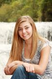 Outdoor Portrait of a pretty blonde girl. In front of a waterfall, smiling close-up, long straight hair, big blue eyes. Sweet sixteen or High School Senior Royalty Free Stock Photo