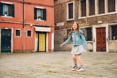 Outdoor portrait of pretty kid girl. Walking through old italian streets, child dancing outside stock photography