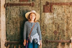 Outdoor portrait of pretty kid girl. Walking through old italian streets, wearing frock, denim jeans and neutral straw hat royalty free stock image