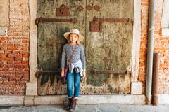 Outdoor portrait of pretty kid girl. Walking through old italian streets, wearing frock, denim jeans and neutral straw hat stock images