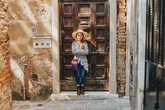 Outdoor portrait of pretty kid girl. Walking through old italian streets, wearing frock, denim jeans and neutral straw hat stock photos