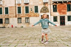 Outdoor portrait of pretty kid girl. Walking through old italian streets, child dancing outside royalty free stock photo