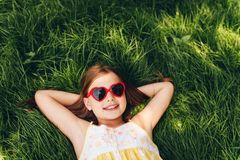 Outdoor portrait of pretty little girl wearing heart shaped sunglasses. Lying on fresh green grass. Party for children, summer fun, happy childhood. Top view Royalty Free Stock Photos