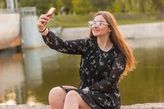 Outdoor portrait of pretty student girl taking a selfie.Beautiful urban woman taking picture of herself, selfie royalty free stock photography