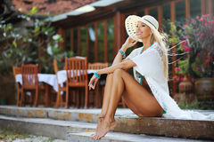 Outdoor portrait of pretty tanned young blonde woman in white dr Royalty Free Stock Photography