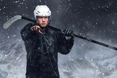 Hockey player in a snow storm. Outdoor portrait of professional hockey player in a snow storm stock images