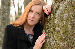 Outdoor portrait of red haired woman with green eyes. A young wo Royalty Free Stock Photography