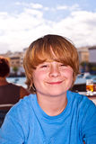 Outdoor portrait of relaxed cute young boy. Looking positive and friendly Stock Image