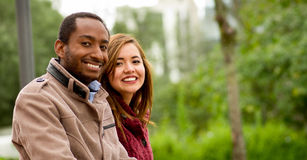 Outdoor portrait of romantic and happy interracial young couple in park Royalty Free Stock Photo