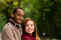 Outdoor portrait of romantic and happy interracial young couple in park Royalty Free Stock Images